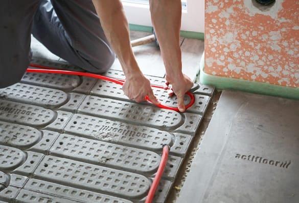 Foto vom Einlegen der Rohre der Actifloor Fußbodenheizung in die Wärmeleitplatten